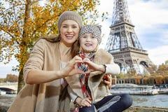 A mãe e a filha em Paris que mostra o coração deram forma às mãos Foto de Stock Royalty Free