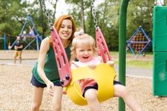 Mãe e filha em um balanço que tem o divertimento no campo de jogos do parque Fotos de Stock Royalty Free