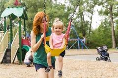 Mãe e filha em um balanço que tem o divertimento no campo de jogos do parque Fotos de Stock
