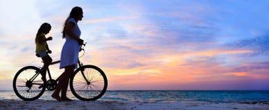 Mãe e filha em uma bicicleta fotografia de stock