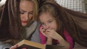 A mãe e a filha encontram-se em uma cama sob uma cobertura e leem-se um livro video estoque