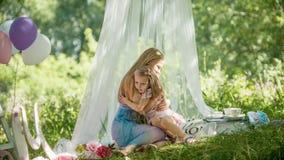 A mãe e a filha estão abraçando no parque - piquenique e aniversário imagens de stock royalty free