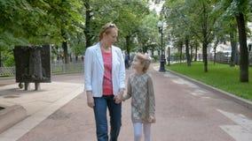 A mãe e a filha estão andando no parque, tendo o divertimento video estoque