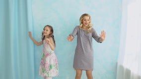 A mãe e a filha estão dançando ao lado da janela Divertimento e alegria video estoque