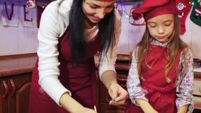 A mãe e a filha estão decorando com mástique do açúcar um queque do Natal filme