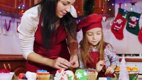 A mãe e a filha estão decorando com mástique do açúcar um queque do Natal video estoque