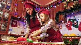 A mãe e a filha estão fazendo decorações com mástique do açúcar para o queque video estoque
