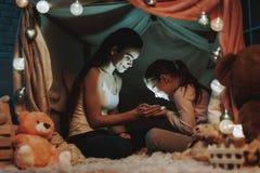 A mãe e a filha estão guardando uma luz nas mãos imagens de stock