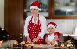A mãe e a filha estão preparando o pão-de-espécie para o Natal Fotos de Stock