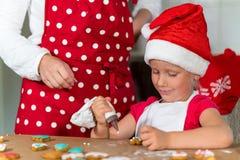 A mãe e a filha estão preparando o pão-de-espécie para o Natal imagem de stock