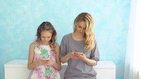 A mãe e a filha estão sentando próximos um do outro a vista em seus telefones e não falam vídeos de arquivo