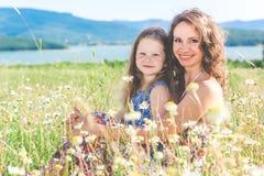 A mãe e a filha estão sentando-se no campo da camomila Fotos de Stock