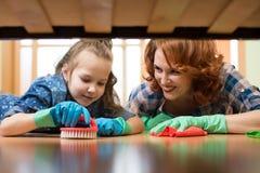 A mãe e a filha fazem a limpeza na casa A menina da mulher feliz e da criança pequena limpou o assoalho foto de stock