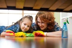 A mãe e a filha fazem a limpeza na casa A menina da mulher feliz e da criança pequena limpou o assoalho fotografia de stock