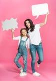 Mãe e filha felizes com as bolhas vazias do discurso que levantam no rosa Foto de Stock