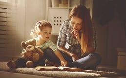 A mãe e a filha felizes da família leram um livro na noite Fotografia de Stock