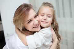 A mãe e a filha felizes estão abraçando em casa imagens de stock royalty free