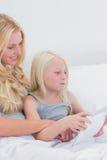 Mãe e filha felizes que usa uma tabuleta Fotos de Stock Royalty Free
