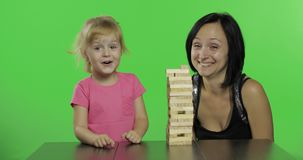 A mãe e a filha jogam o jenga A criança puxa blocos de madeira da torre filme