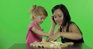 A mãe e a filha jogam o jenga Criança que faz uma torre dos blocos de madeira filme