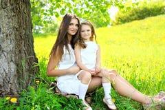 Mãe e filha junto na grama perto da árvore no verão Fotografia de Stock