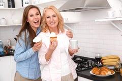 A mãe e a filha junto weekend em casa o chá bebendo que come queques fotos de stock royalty free