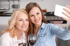 A mãe e a filha junto weekend em casa tomando fotos do selfie imagem de stock
