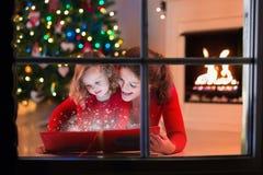 A mãe e a filha leram um livro na chaminé na Noite de Natal Foto de Stock Royalty Free