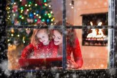 A mãe e a filha leram um livro na chaminé na Noite de Natal Imagem de Stock Royalty Free