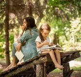 A mãe e a filha leram um livro no parque Fotos de Stock Royalty Free