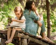 A mãe e a filha leram um livro no parque Imagens de Stock Royalty Free