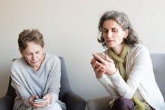 Mãe e filha mais idosas que usa smartphones Fotografia de Stock Royalty Free