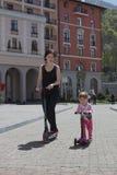 A mãe e a filha montam em um 'trotinette' na cidade Fotos de Stock Royalty Free