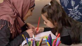 A mãe e a filha muçulmanas encontram-se no sofá e na pintura com lápis coloridos, conceito de família feliz, conforto home no vídeos de arquivo