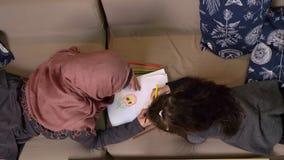 A mãe e a filha muçulmanas encontram-se no sofá e na pintura com lápis coloridos, conforto home no fundo, tiro superior video estoque