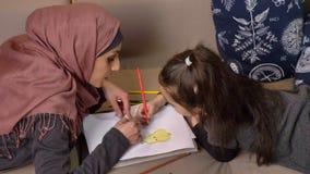 A mãe e a filha muçulmanas encontram-se no sofá e na pintura com lápis coloridos, conforto home no fundo, vista lateral 50 vídeos de arquivo