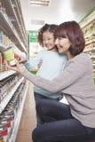 Mãe e filha na compra do supermercado, ajoelhando-se e olhando um produto Fotografia de Stock