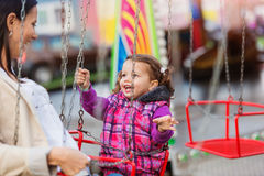 Mãe e filha na feira de divertimento, passeio chain do balanço Imagens de Stock Royalty Free