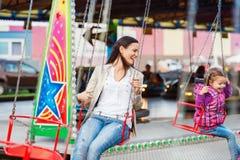 Mãe e filha na feira de divertimento, passeio chain do balanço Fotografia de Stock