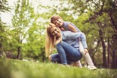 Mãe e filha na grama verde imagem de stock