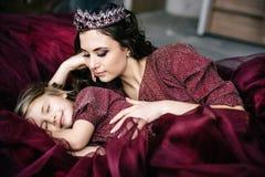 A mãe e a filha na imagem da rainha e da princesa vestem-se Fotografia de Stock Royalty Free