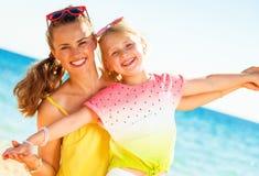 Mãe e filha na moda de sorriso no litoral que tem o tempo do divertimento fotos de stock royalty free