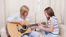 Mãe e filha na sala de visitas que aprendem jogar em uma guitarra acústica filme