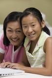 Mãe e filha na sala de visitas usando o retrato do portátil junto fotografia de stock royalty free