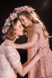 Mãe e filha nas grinaldas florais que abraçam e que tocam nas testas Foto de Stock Royalty Free