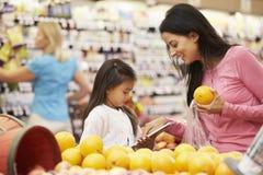 Mãe e filha no contador do fruto no supermercado com lista fotografia de stock