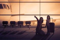 Mãe e filha no salão do aeroporto imagens de stock