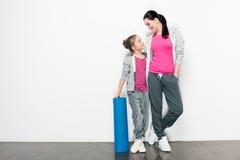 Mãe e filha no sportswear que está com esteira da ioga e que olha se imagens de stock
