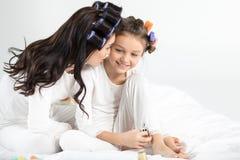 Mãe e filha nos encrespadores e nos pijamas que sentam-se junto na cama fotografia de stock