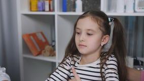 Mãe e filha nova ao doutor O doutor fêmea mede a temperatura da criança usando um eletrônico filme